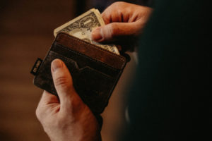 Decorative image of person putting money in wallet