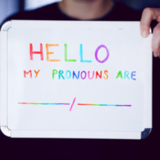 """Photo of person holding up sign with text """"Hello, my pronouns are: __/__"""""""