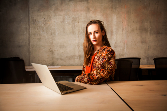 Photo of person sitting at laptop