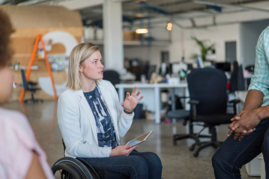 Decorative photo of person in wheelchair talking to colleague